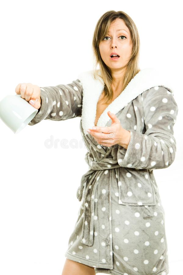 De blondevrouw in grijze peignoir met punten toont lege mok - nr stock afbeeldingen