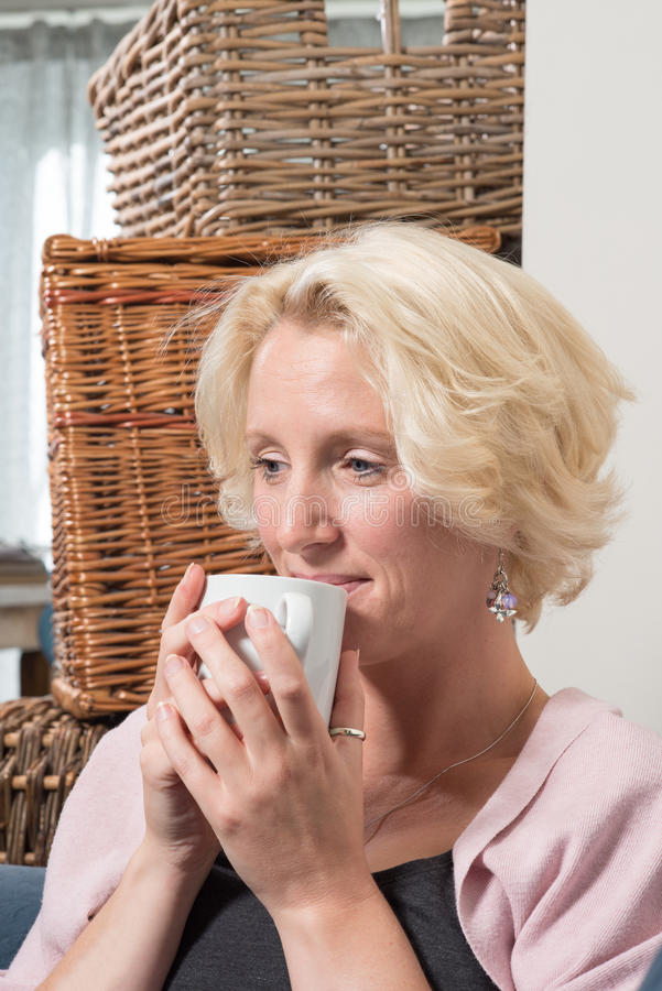 De blondevrouw houdt Mok van Drank en glimlacht met Tevredenheid stock afbeeldingen