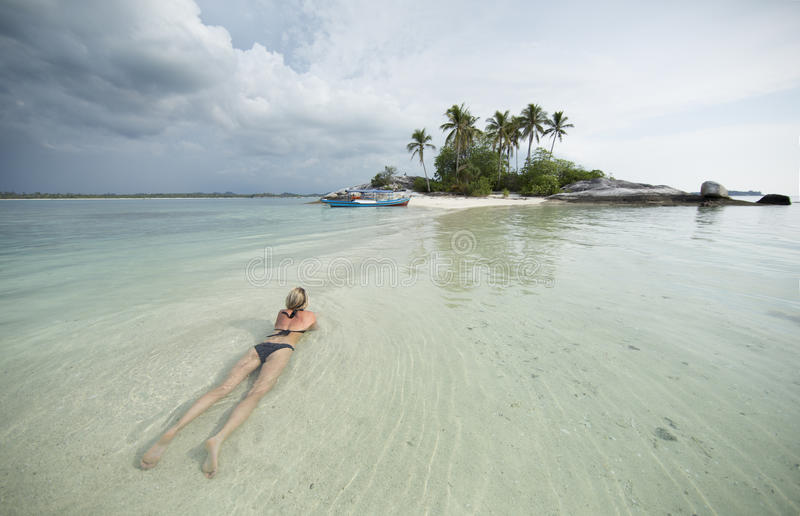 De blondevrouw legt in water van oceaan, dichtbij aan een kleine eiland en een boot stock foto's