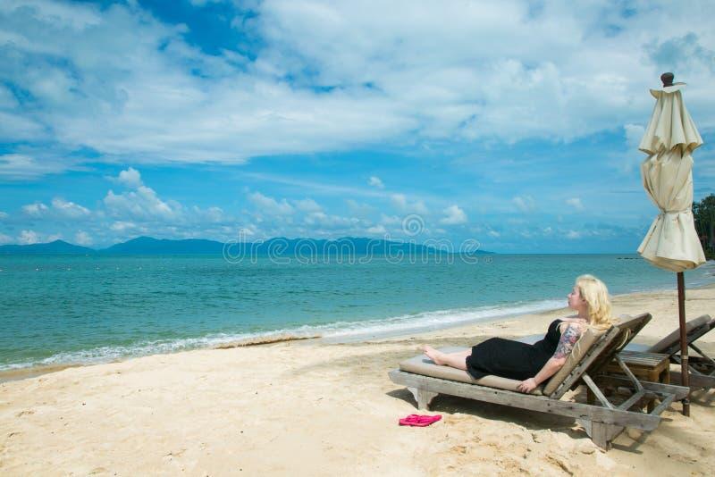 De blondevrouw ligt op een deckchair op het strand royalty-vrije stock afbeelding
