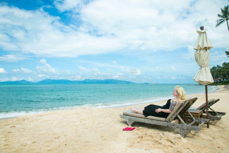 De blondevrouw ligt op een deckchair op het strand royalty-vrije stock foto's