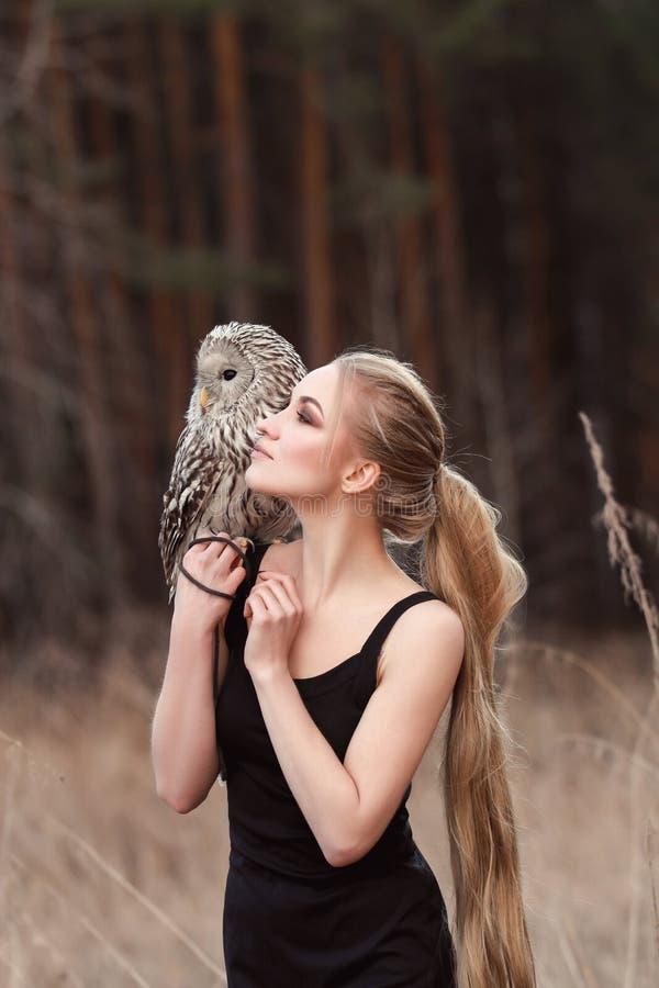 De blondevrouw met een uil in haar handen loopt in het hout in de herfst en de lente Lang haarmeisje, romantisch portret met uil  royalty-vrije stock foto's