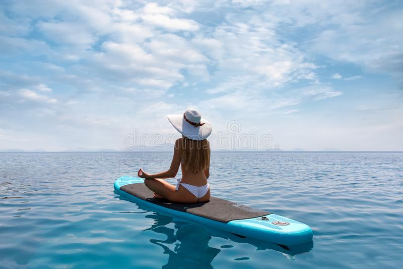 De blondevrouw ontspant in een yogapositie inzake een tribune op SUP van de peddelraad stock foto's