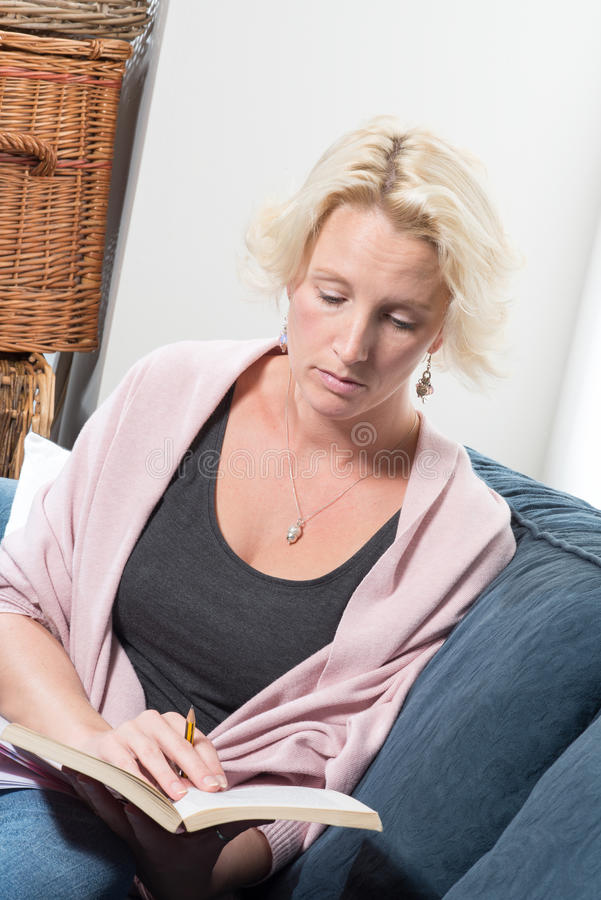 De blondevrouw op Bank of Laag houdt Boek en Potlood royalty-vrije stock afbeeldingen