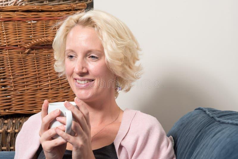 De blondevrouw op Bank met Hete Drank glimlacht EXEMPLAARruimte stock foto