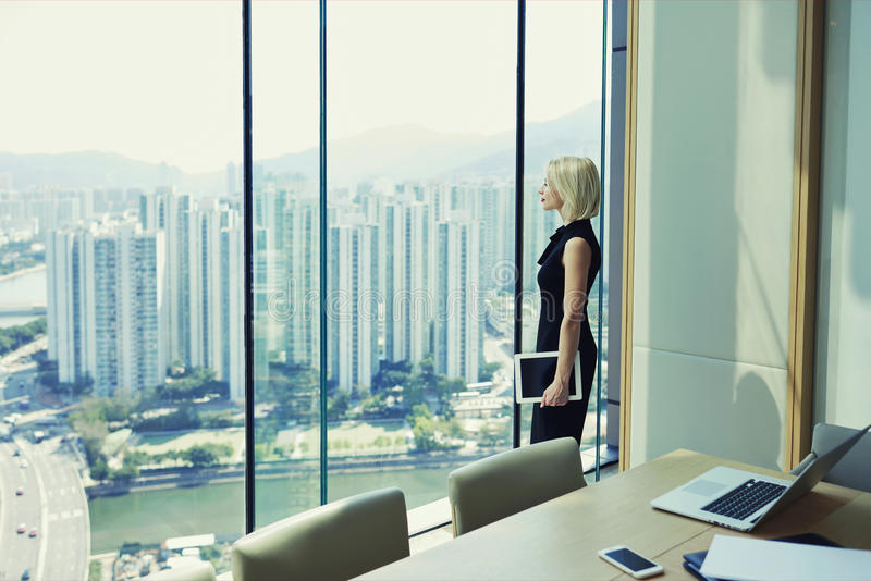 De blondevrouw trotse CEO houdt aanrakingsstootkussen en kijkt in bureauvenster met cityscape royalty-vrije stock foto's