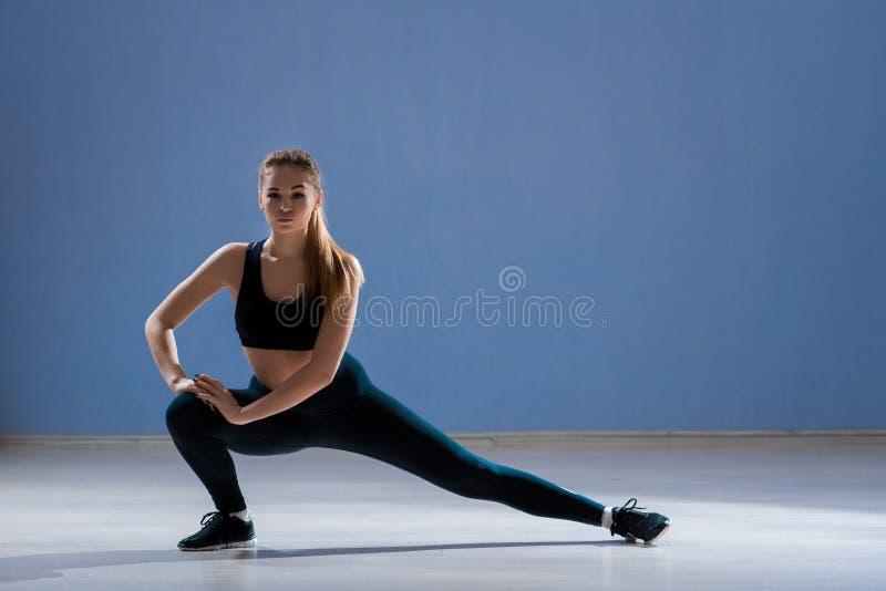 De blondevrouw voert oefeningen in een sporthal uit royalty-vrije stock afbeelding
