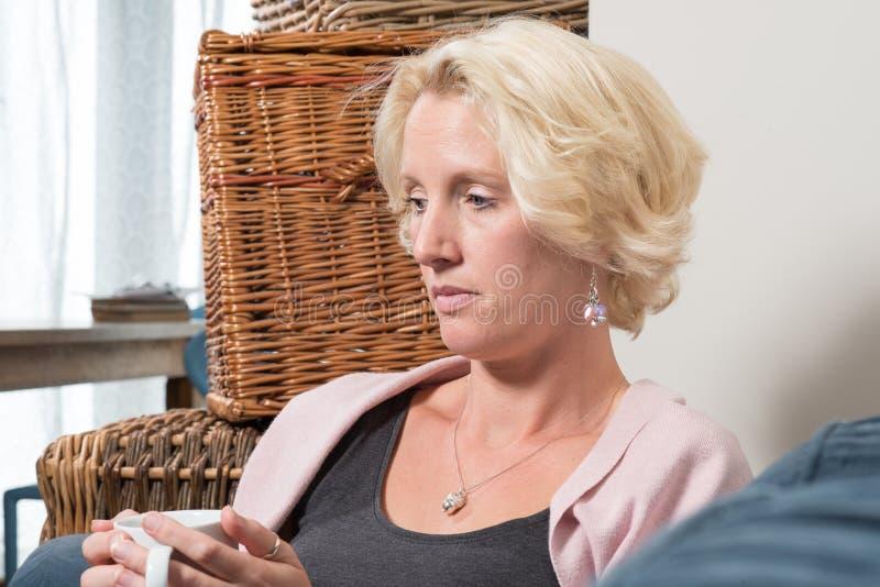 De blondevrouw zit bij Sofa Holding Mug en het Denken royalty-vrije stock afbeelding