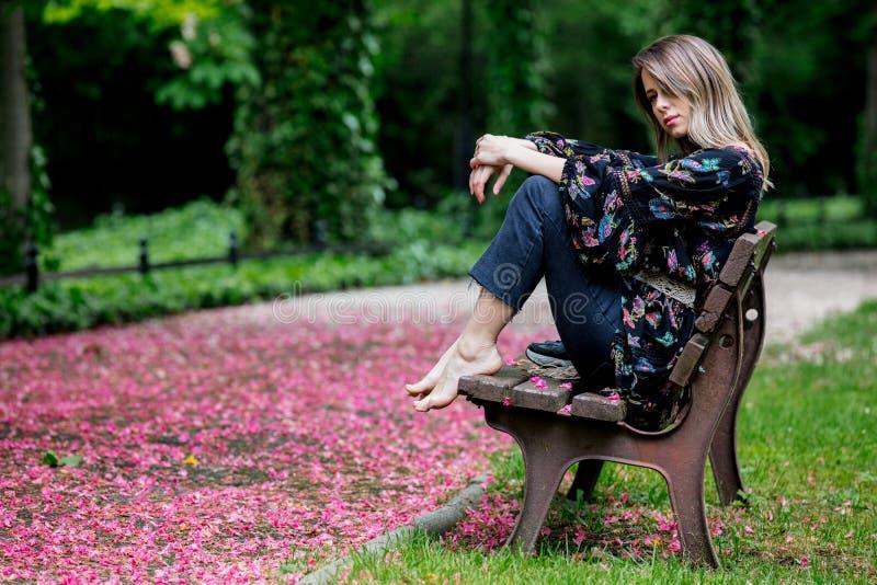 De blootvoetse vrouw zit op een bank bij steeg met bloesembomen royalty-vrije stock afbeelding