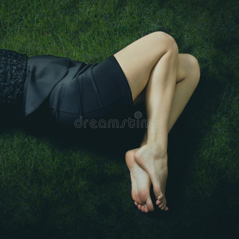 Download De Blootvoetse Vrouw In Zwarte Kleding Ligt Op Gras Stock Afbeelding - Afbeelding bestaande uit art, sluit: 107701937