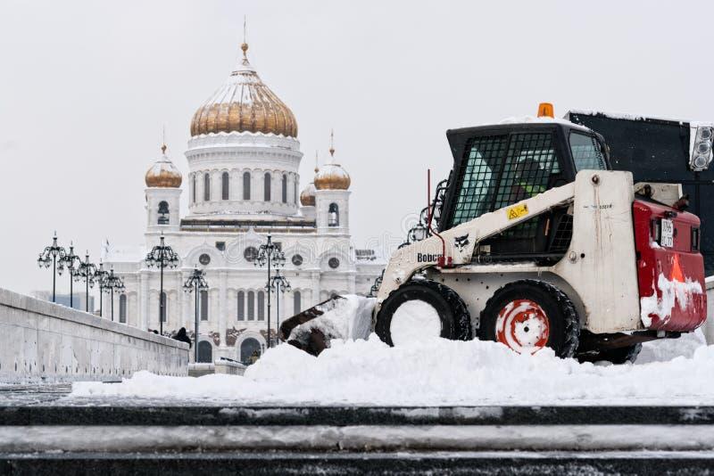 De Bobcatlader verwijdert sneeuw uit Patriarchbrug stock foto's
