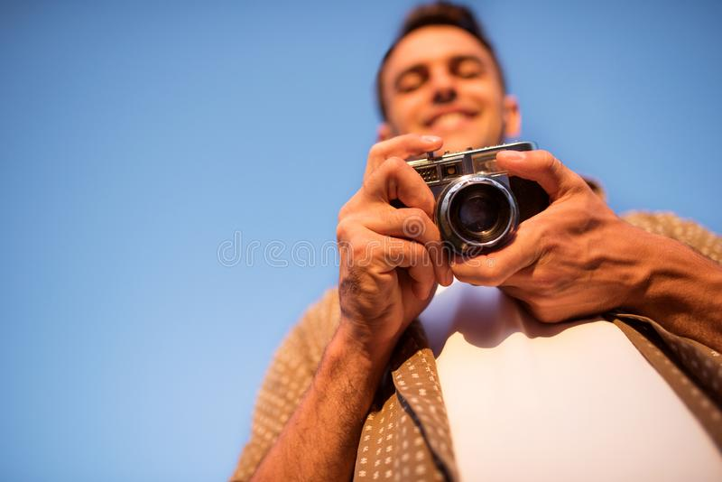 De bodemmening van de glimlachende knappe jonge mens met uitstekende camera, neemt een beeld op hemelachtergrond De herfst De zom royalty-vrije stock afbeeldingen