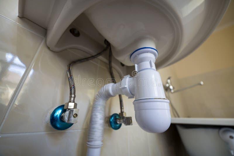 De bodemmening van nieuwe witte wasbakgootsteen verbond met riool op achtergrond van badkamers lichte beige keramische tegels pro stock afbeelding