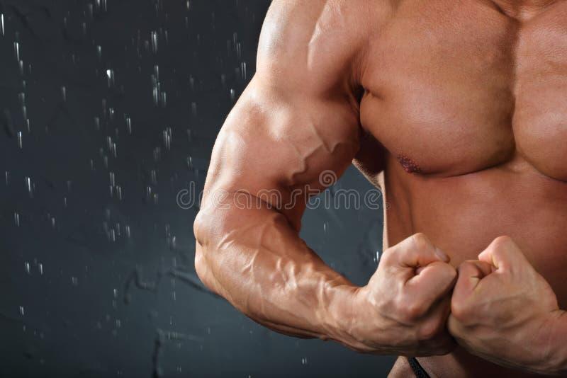 De bodybuilder bevindt zich en toont spieren royalty-vrije stock foto's