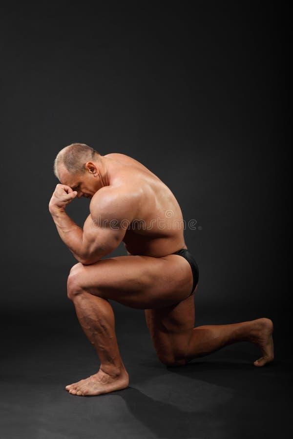 De bodybuilder bevindt zich op één knie en denkt royalty-vrije stock foto