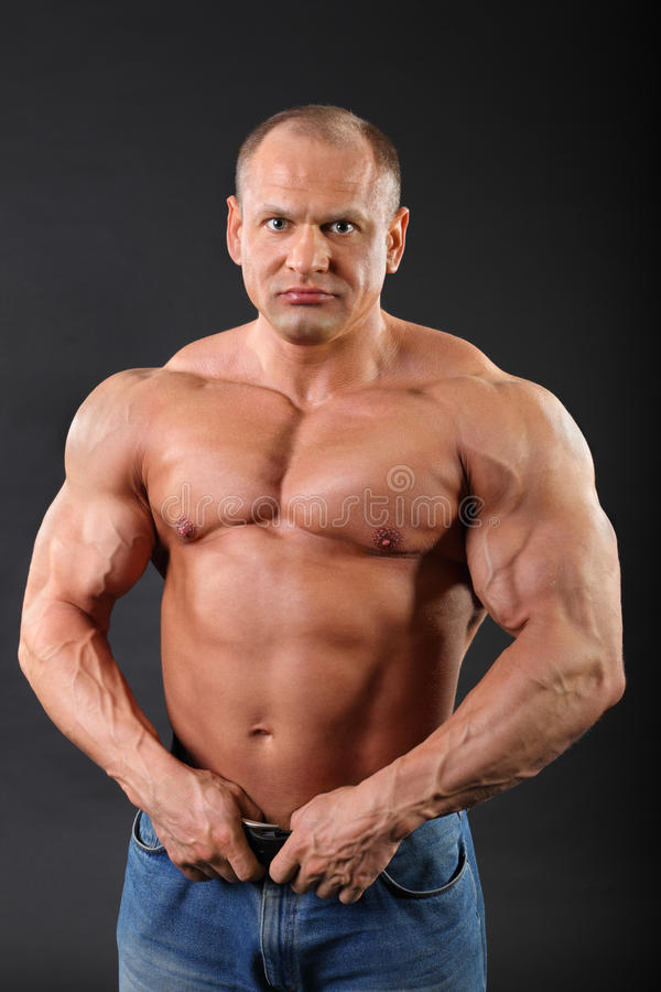 De bodybuilder die in jeans draagt houdt zijn riem royalty-vrije stock foto's