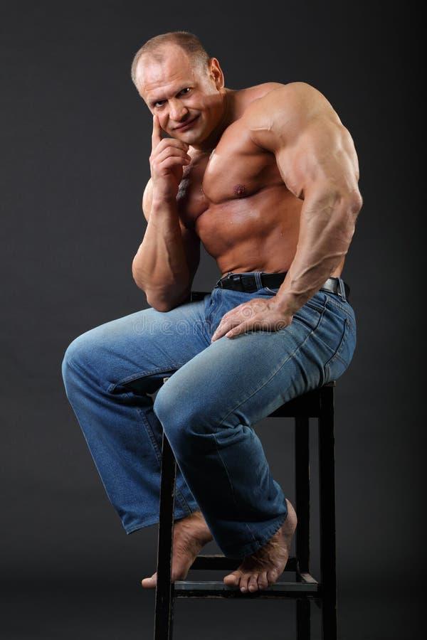 De bodybuilder die in jeans draagt zit bij kruk royalty-vrije stock afbeeldingen