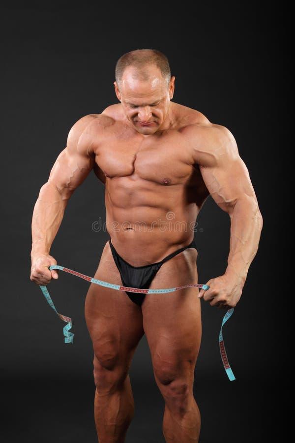 De bodybuilder houdt het meten van band en kijkt neer stock foto's
