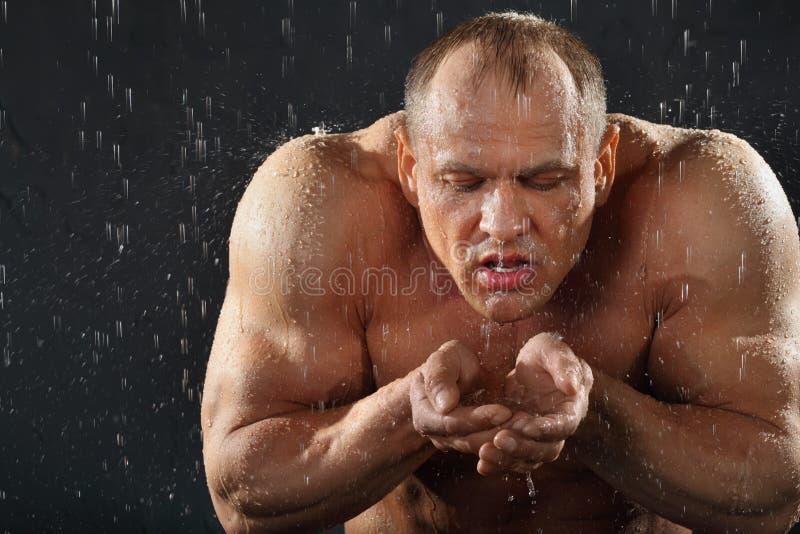 De bodybuilder in regen drinkt water van handen stock fotografie