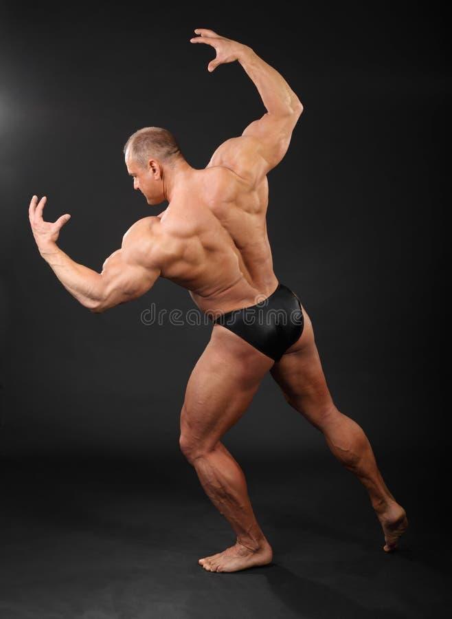 De bodybuilder toont spieren van wapens en rug royalty-vrije stock afbeeldingen