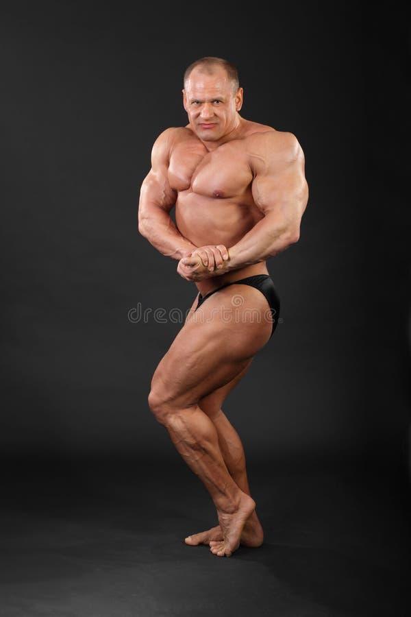 De bodybuilder toont wapens en benenspieren aan royalty-vrije stock afbeelding