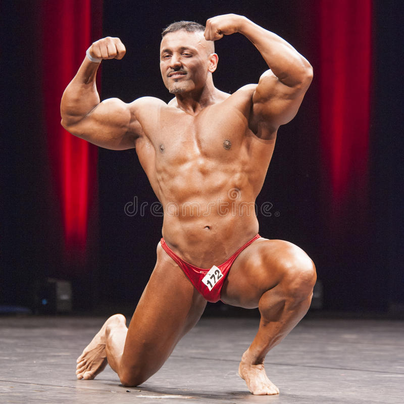 De bodybuilder toont zijn voor dubbele bicepsen op stadium stellen royalty-vrije stock afbeeldingen