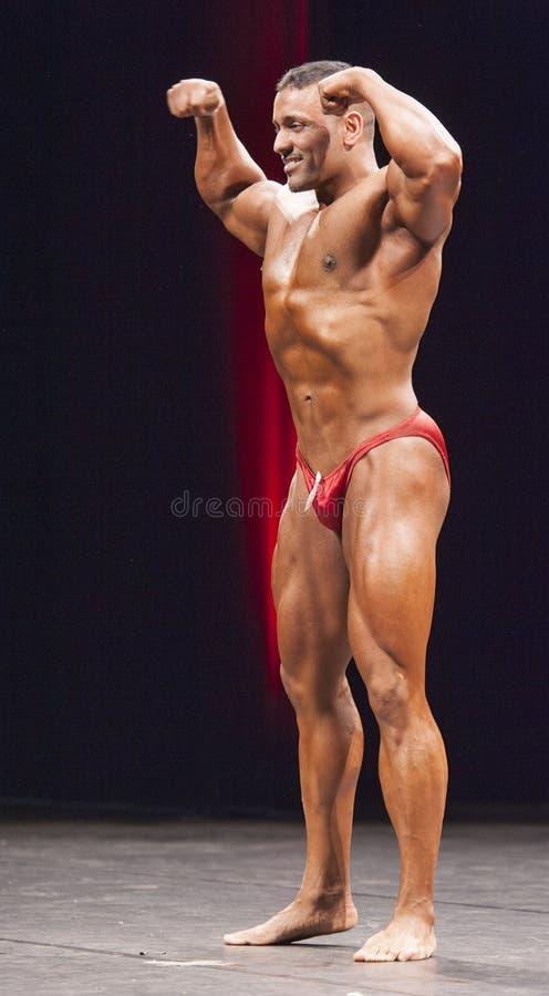 De bodybuilder toont zijn voor dubbele bicepsen op stadium stellen stock foto's