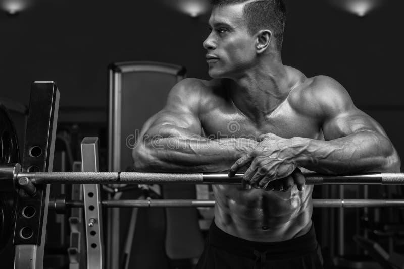 De bodybuilder treft voorbereidingen om oefeningen met barbell te doen stock foto's