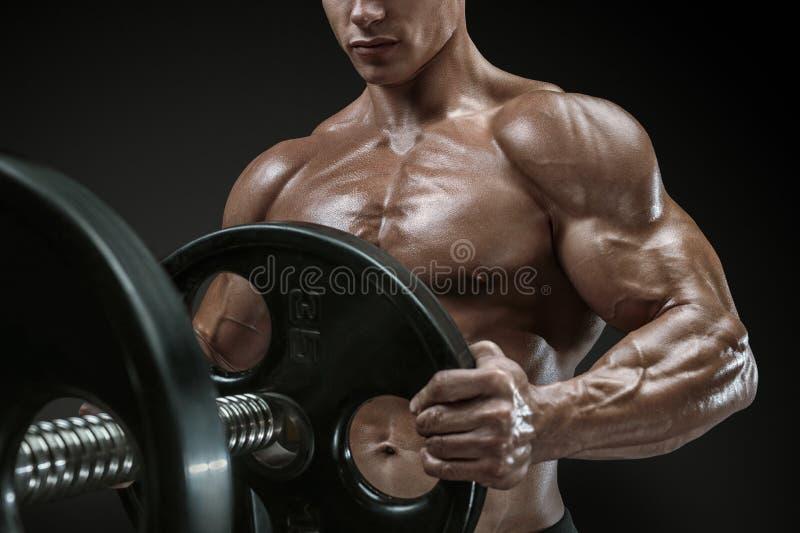 De bodybuilder treft voorbereidingen om oefeningen met barbell te doen stock fotografie