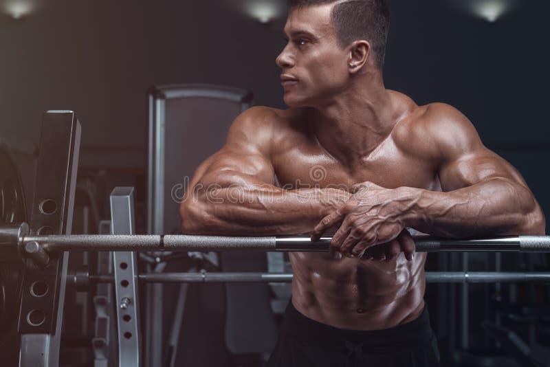 De bodybuilder treft voorbereidingen om oefeningen met barbell te doen royalty-vrije stock afbeelding