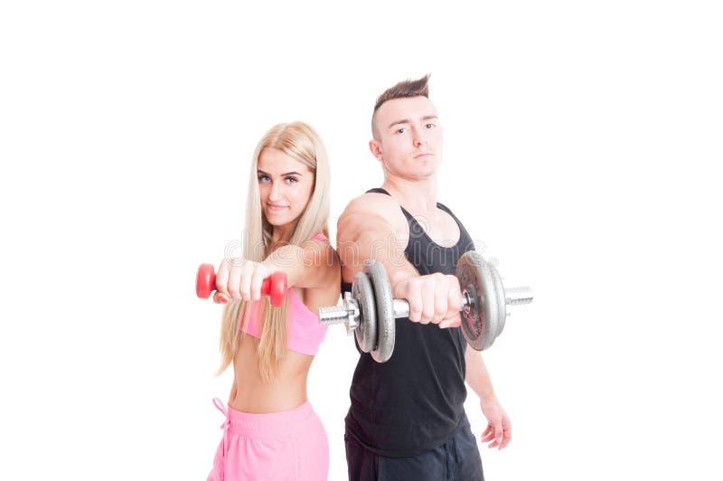 De bodybuildervriend met de sexy holding van het geschiktheidsmeisje weegt stock foto's