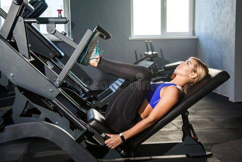 De Bodybuildingsvrouw ligt op simulatorplatform stock foto