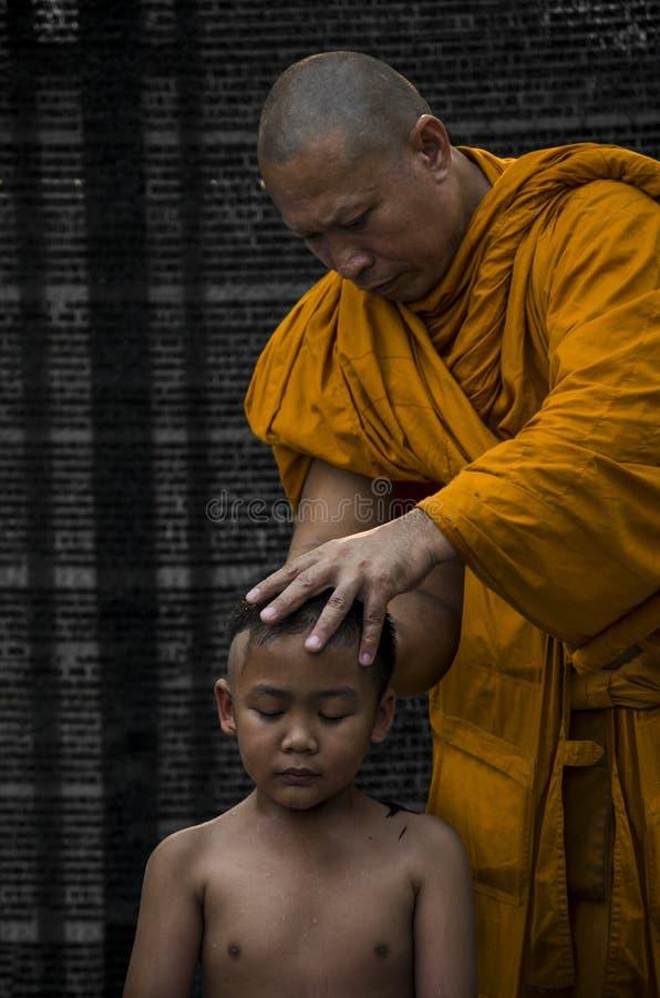 De boeddhistische jongen werd geschoren door monnik stock afbeelding