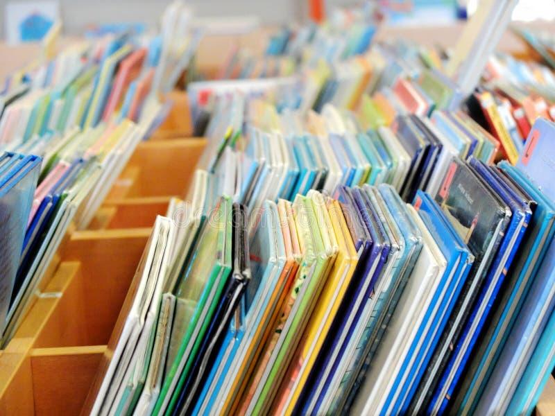 De boeken die van heel wat kleurrijke kinderen zich op de openbare bibliotheekplank bevinden royalty-vrije stock foto's