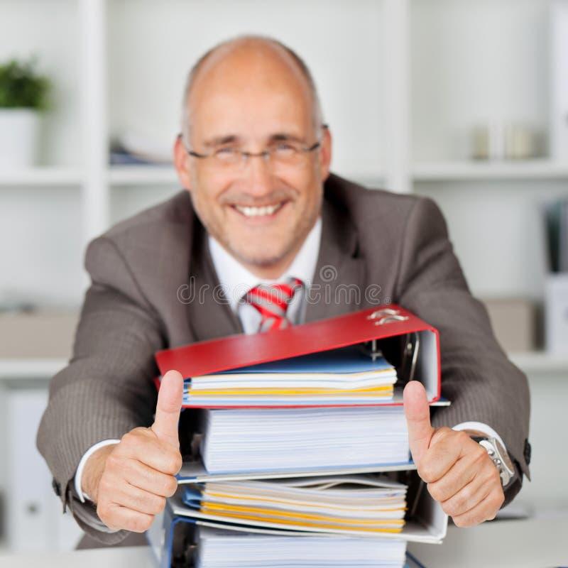 De Boeken Gesturing van zakenmanwith stack of beduimelt omhoog royalty-vrije stock afbeelding