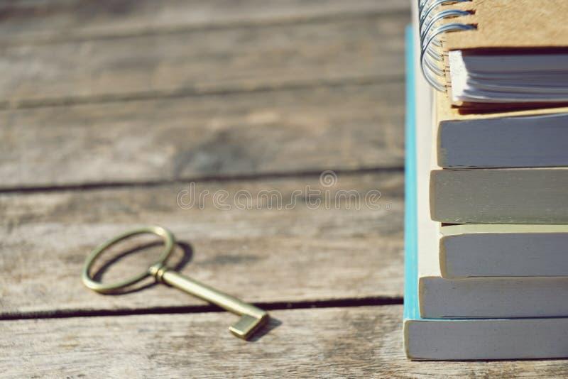 De boeken stapelen en sleutels op houten lijstachtergrond, sleutel van succesconcept stock afbeeldingen