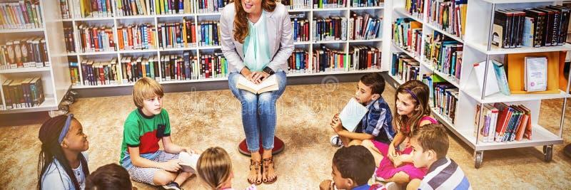De boeken van de leraarslezing aan haar studenten stock foto's