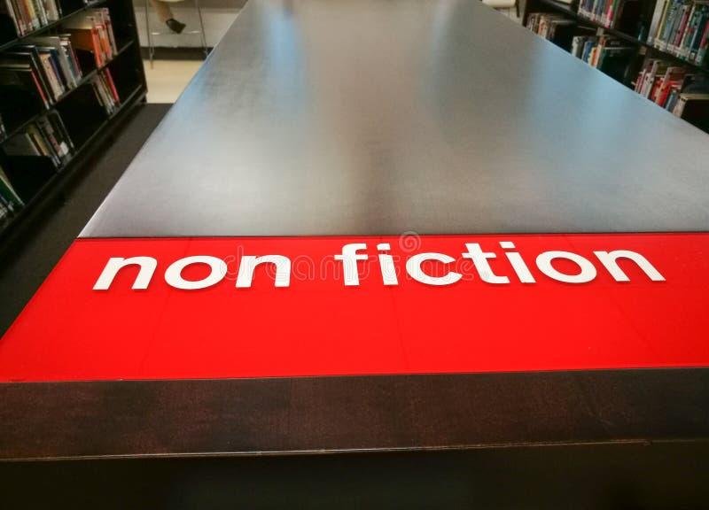 De boekenrekken tonen Non-fictie rood teken in een bibliotheek stock foto's