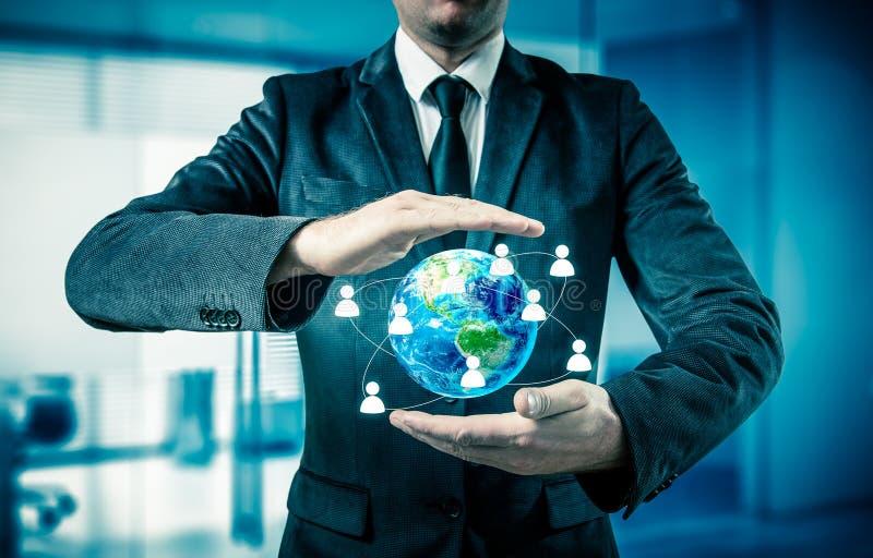 De bol van de zakenmanholding in zijn handen Het concept personeelsbeheer rond de wereld royalty-vrije stock fotografie