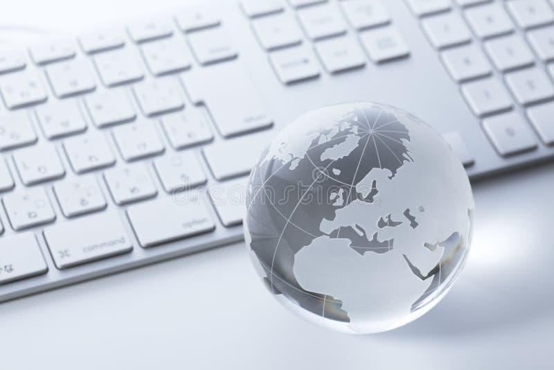 De bol van het glas op een toetsenbord stock foto