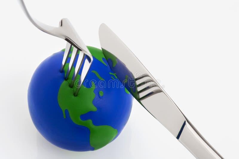 De bolbal van de wereld met vork en mes stock afbeelding