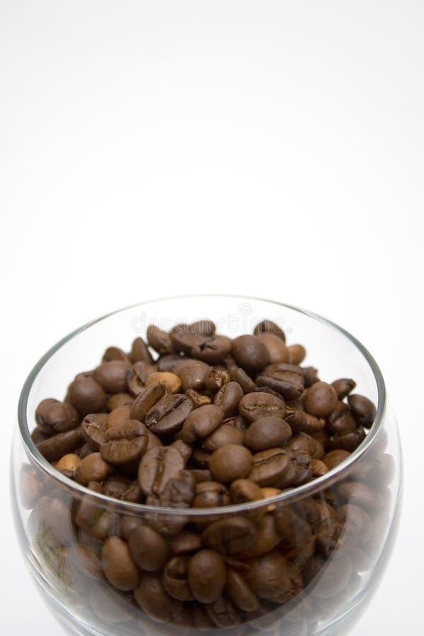 De Bonen van de koffie in de Kom van het Glas stock foto