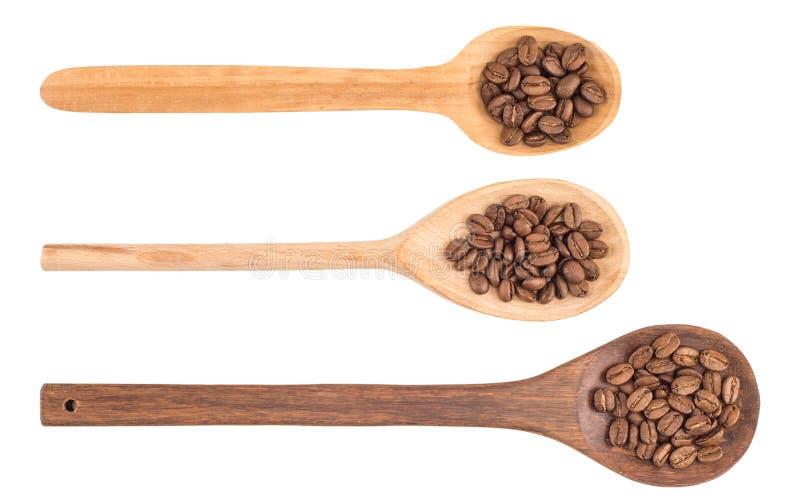 De bonen van de koffie in houten lepel stock afbeeldingen
