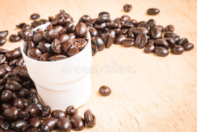 De bonen van de koffie op houten achtergrond stock fotografie