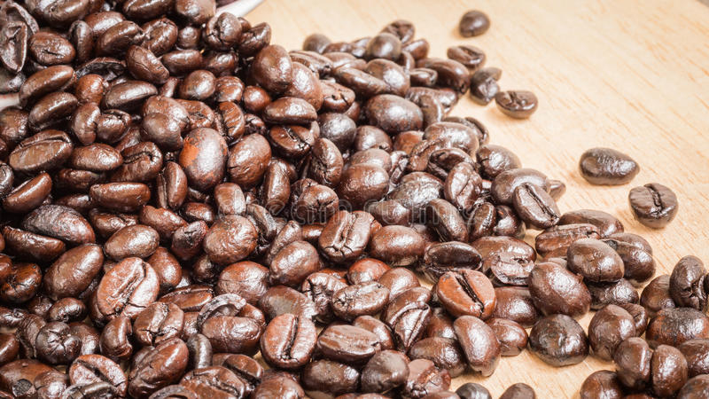 De bonen van de koffie op houten achtergrond royalty-vrije stock afbeelding