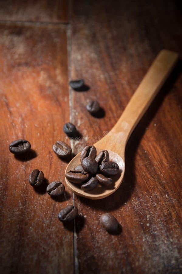 De bonen van de koffie op houten lepel stock afbeeldingen