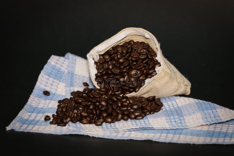 De bonen van de koffie in zak Donkere achtergrond stock afbeeldingen