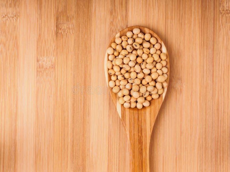 De bonen van de soja in houten lepel stock afbeeldingen