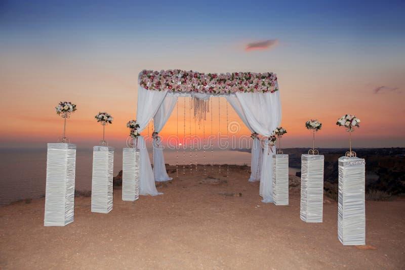 De boog van de huwelijksceremonie met bloemstuk met wit gordijn royalty-vrije stock afbeeldingen