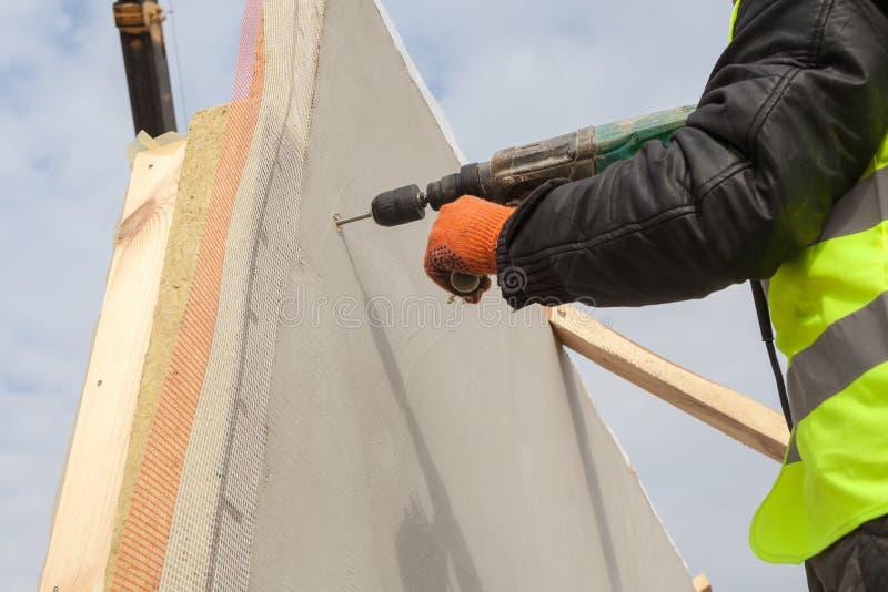 De boor van het de arbeidersgebruik van de Rooferbouwer om een gat in structureel Geïsoleerd Comité te maken stock afbeelding